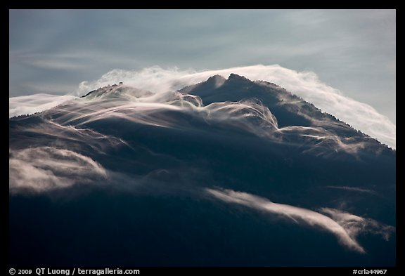 Cloudcap over backlit Mt Scott summit. Crater Lake National Park, Oregon, USA.