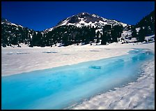 Turquoise melting snow in lake Helen and Lassen Peak, late spring. Lassen Volcanic National Park, California, USA.