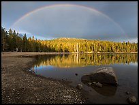 Rainbow in dark sky above Juniper Lake. Lassen Volcanic National Park, California, USA.