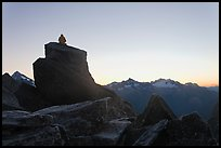 Man sitting on rock contemplates mountains at sunrise, North Cascades National Park. Washington, USA.