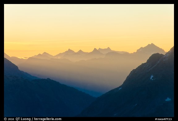 First sunrays lighting peaks above Cascade Pass, North Cascades National Park. Washington, USA.