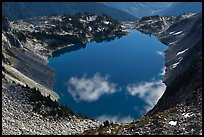 Fluffy clouds reflected in blue lake, North Cascades National Park.  ( color)
