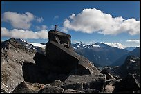Man sitting on rock photographs mountain panorama, North Cascades National Park. Washington, USA.