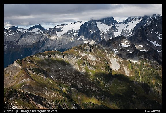 Cloud-capped mountains in dabbled light, North Cascades National Park.  (color)