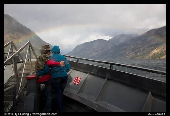 Couple at bow of boat looking at rainbow over Lake Chelan, North Cascades National Park Service Complex.  (color)