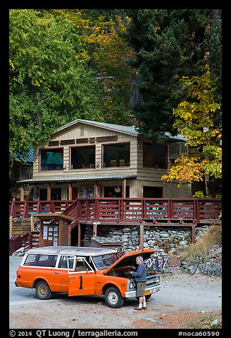 Man fixing old car in front of North Cascades Lodge, Stehekin, North Cascades National Park Service Complex.  (color)