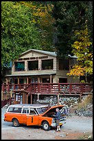 Man fixing old car in front of North Cascades Lodge, Stehekin, North Cascades National Park Service Complex.  ( color)
