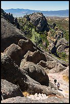 Hikers approaching cliff with steps carved in stone. Pinnacles National Park, California, USA.
