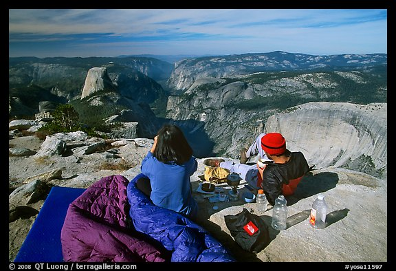 Backpackers eat breakfast, looking at Yosemite Valley from Clouds Rest. Yosemite National Park (color)