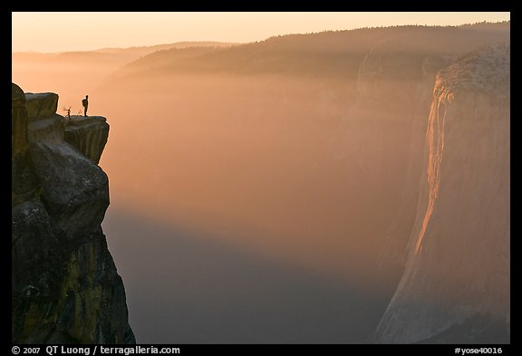 Hiker standing on top of sheer cliff at Taft point. Yosemite National Park (color)