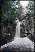 Snow-covered boulder and base of Chilnualna Falls. Yosemite National Park, California, USA.