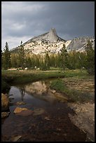 Cathedral Peak reflected in stream under stormy skies. Yosemite National Park, California, USA.