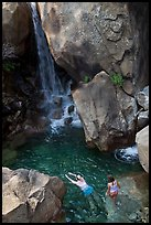 Swimmers in a pool at the base of Wapama falls, Hetch Hetchy. Yosemite National Park, California, USA.