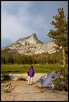 Camper standing next to tent looks at Cathedral Peak, evening. Yosemite National Park, California, USA. (color)