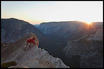Hiker looking over the edge of the Diving Board, sunset. Yosemite National Park, California, USA.