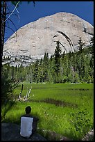Hiker sitting at Lost Lake on west side Half-Dome. Yosemite National Park, California, USA. (color)