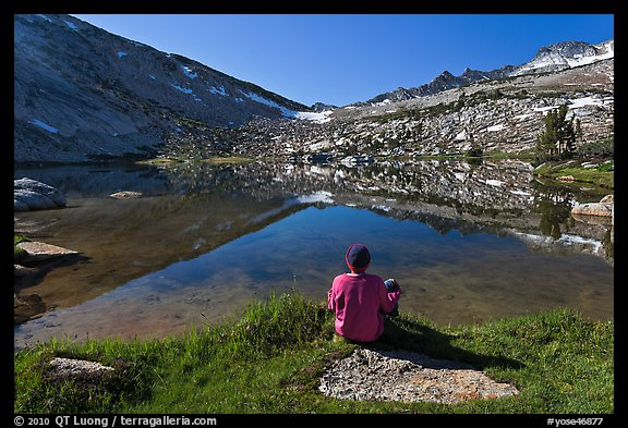 Hiker sitting by alpine lake, Vogelsang. Yosemite National Park (color)