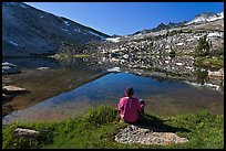 Hiker sitting by alpine lake, Vogelsang. Yosemite National Park, California, USA.
