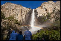 Tourists looking at Bridalvail Fall rainbow. Yosemite National Park, California, USA. (color)