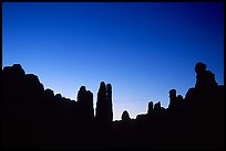 Sandstone pillars in Klondike Bluffs seen as silhouettes at dusk. Arches National Park, Utah, USA.