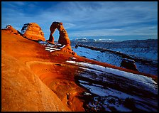 Sandstone bowl, Delicate Arch, and La Sal Mountains with snow, sunset. Arches National Park, Utah, USA.
