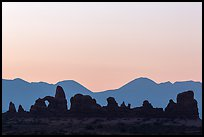 Turret Arch, spires, and mountains at dawn. Arches National Park, Utah, USA. (color)
