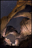 Person lighting up Double Arch at night. Arches National Park, Utah, USA. (color)