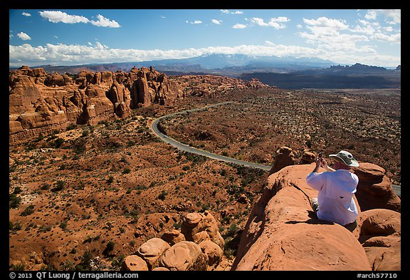 Tourist taking picture from top of fin. Arches National Park (color)