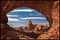 Family in the North Window span. Arches National Park, Utah, USA. (color)