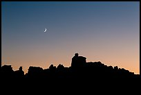 Crescent moon at sunset and Doll House spires. Canyonlands National Park, Utah, USA. (color)