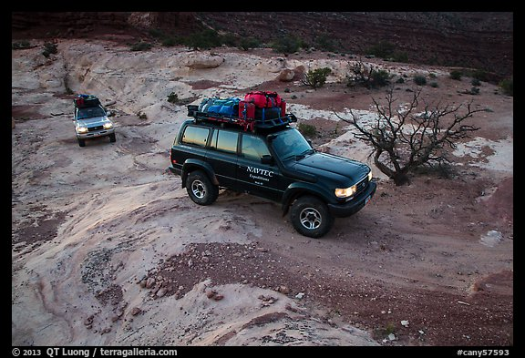 4WD vehicles driving over rock at dusk in Teapot Canyon. Canyonlands National Park (color)