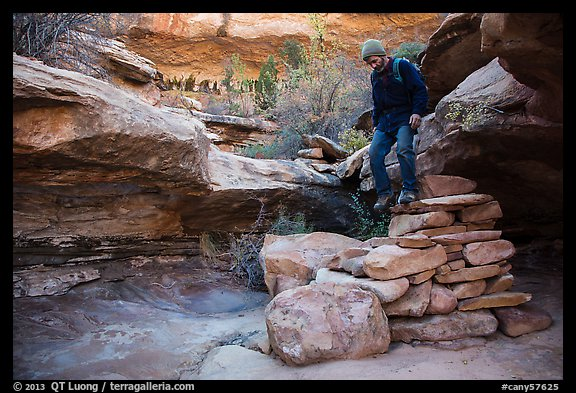 Hiker stepping down on primitive stairs, Maze District. Canyonlands National Park (color)