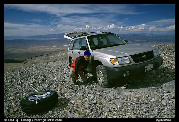 Man changing a flat tire on remote spot at top of Mt Washington. Great Basin National Park (color)