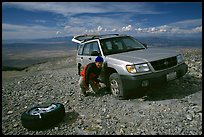 Man changing a flat tire on remote spot at top of Mt Washington. Great Basin National Park, Nevada, USA. (color)