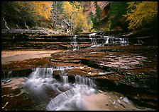 North Creek flowing over red travertine terraces in autumn. Zion National Park, Utah, USA.