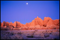 Moon and eroded badlands, Cedar Pass, dawn. Badlands National Park, South Dakota, USA.