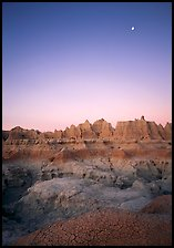 Mud cracks, badlands, and moon at dawn. Badlands National Park, South Dakota, USA.