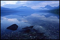 Rocks, peebles, and mountain reflections in lake McDonald. Glacier National Park, Montana, USA.