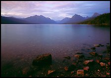 Rocks, Lake Mc Donald, and mountains at sunset. Glacier National Park, Montana, USA.