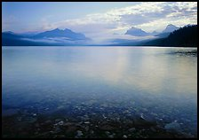 Lake McDonald with clouds and mountains reflected in early morning. Glacier National Park, Montana, USA.