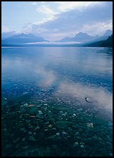 Pebbles, lake Mc Donald, and foggy mountain range, early morning. Glacier National Park, Montana, USA.