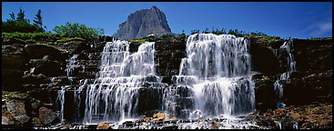 Waterfall flowing over dark rock and peak. Glacier National Park, Montana, USA.
