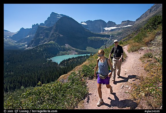 Couple hiking on trail, with Grinnell Lake below. Glacier National Park (color)