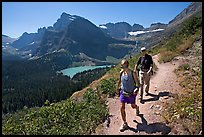 Couple hiking on trail, with Grinnell Lake below. Glacier National Park, Montana, USA. (color)