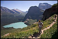 Hikers on trail overlooking Grinnell Lake. Glacier National Park, Montana, USA. (color)
