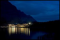 Many Glacier lodge lights reflected in Swiftcurrent Lake at night. Glacier National Park, Montana, USA.