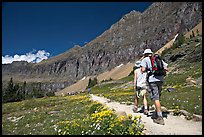 Hikers on trail amongst wildflowers near Hidden Lake. Glacier National Park, Montana, USA. (color)