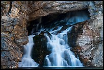 Water flows of opening in cliff face, Running Eagle Falls. Glacier National Park ( color)