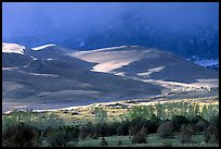 Storm light illuminates portions of the dune field. Great Sand Dunes National Park, Colorado, USA.