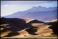 Distant view of dunes and Sangre de Christo mountains in late afternoon. Great Sand Dunes National Park and Preserve, Colorado, USA.